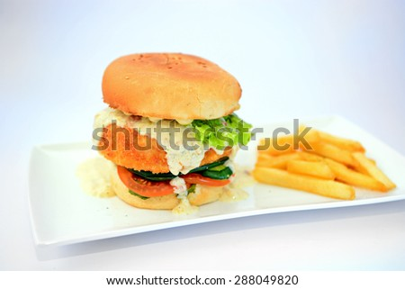 Dory burger with potato chips on white plate - stock photo
