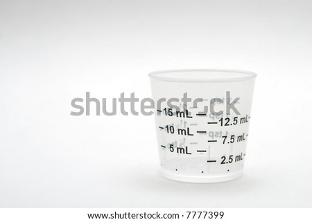 dosage cup with metic measurements displayed - stock photo