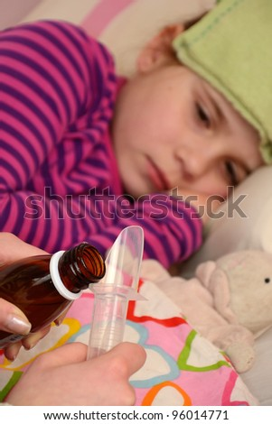 Dosing medicine for sick child girl - stock photo