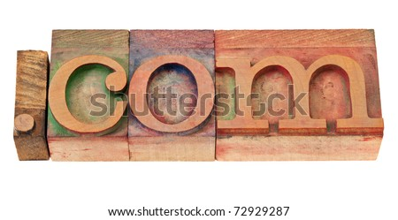 dot com internet commercial domain in vintage wooden letterpress printing blocks, stained by color inks, isolated on white