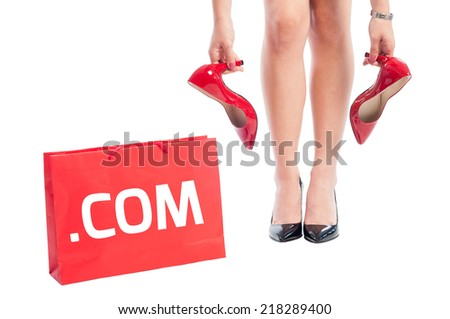 Dot com online shopping for woman shoes concept using red shoping bag and woman holding high heel red shoes - stock photo