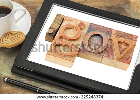 dot gov - internet domain for government in letterpress wood type printing blocks on a digital tablet screen with a cup of coffee - stock photo