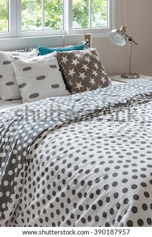 dot pattern blanket on modern bed with lamp in bedroom design