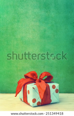 dotted gift box with ribbon on wooden background - stock photo