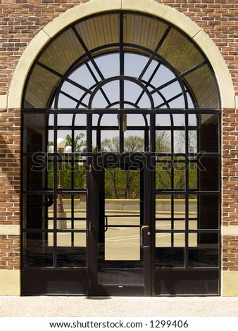 Double arched doorway with brick surrounding looking out to trees - stock photo