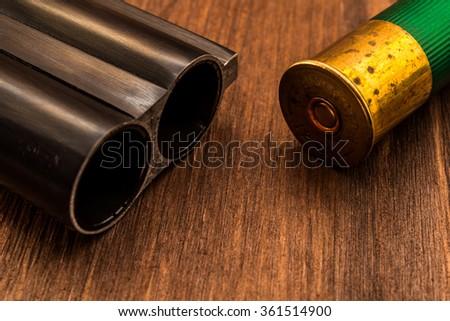 Double-barreled shotgun barrel and green cartridge. Close up view - stock photo