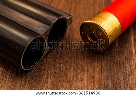 Double-barreled shotgun barrel and red cartridge. Close up view - stock photo