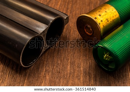 Double-barreled shotgun barrel and two green cartridges. Close up view - stock photo