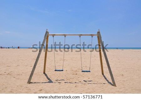 double beach swing over sand and blue sky background, Spain