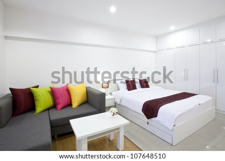Double bed and sofa in the modern interior room