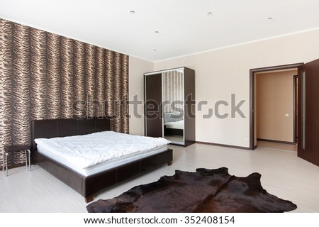 Double  bed in a light spacious upmarket modern bedroom with large windows - stock photo