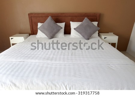 Double bed in the bedroom interior with white and gray pillows and white cloth and brown wall. - stock photo