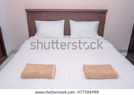 Double bed in the bedroom interior with white and white cloth in hotel room.