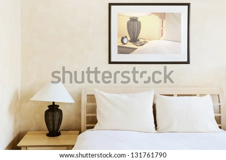 Double Bed In The Bedroom With Desk Lamp Near It - stock photo
