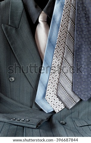 double-breasted pinstripe gray suit or mens sport jacket and shirt with assortment of neckties - stock photo