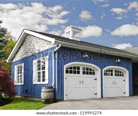 Double car garage with white doors and blue exterior - stock photo