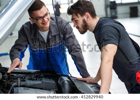 Double check. Two professional car mechanics working at their repair shop - stock photo