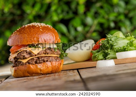 double cheese beef burger with vegetables on wood  - stock photo