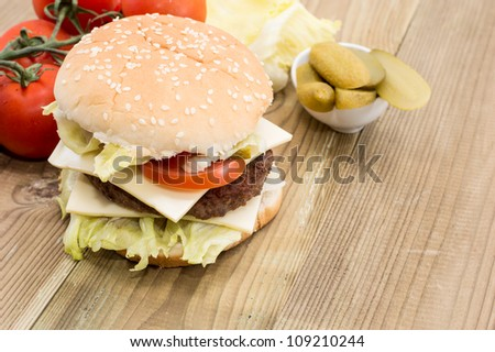 Double Cheeseburger with ingredients on a old wooden table