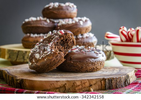 Double chocolate peppermint donuts with candy cane sprinkles sitting rustic wooden plate on festive Christmas breakfast table