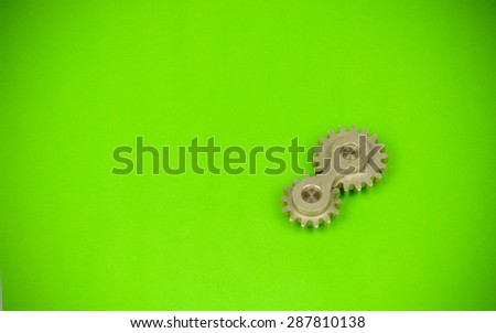 Double cog wheel element on vibrant green paper texture background with vignette corner effect, showing funny playful approach to mechanical dynamics theoretical sciences and heavy industry items - stock photo