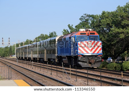 Double-decker commuter train approaching the station in the suburbs - stock photo