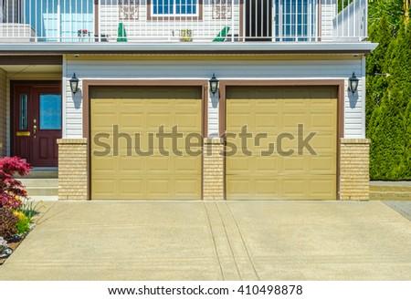 Double doors garage with long driveway. - stock photo