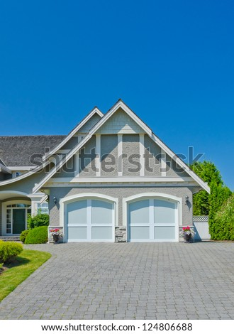 Double doors garage with long driveway. North America. - stock photo