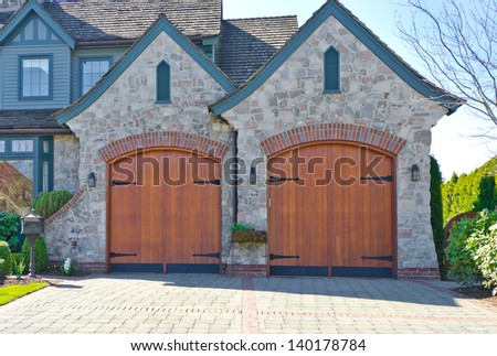 Double doors garage with nicely paved long driveway. North America. - stock photo