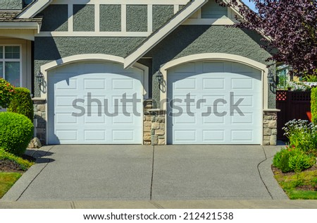 Double doors garage with wide long driveway. - stock photo