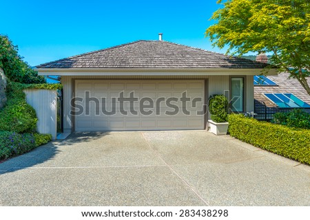 Double doors garage with wide, long driveway. North America. - stock photo