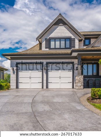 Double doors garage with wide, long driveway. North America. Canada.
