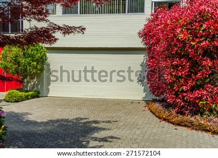 Double doors garage with wide, nicely paved driveway. North America. Canada. - stock photo