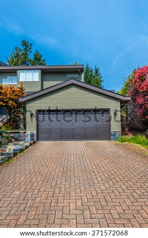 Double doors garage with wide, nicely paved driveway. North America. Canada. Vertical. - stock photo