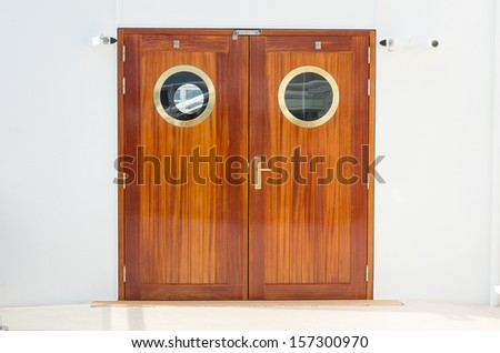 Double doors with brass fittings with a white wall background - stock photo
