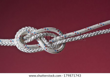 double eight rope knot isolated on red background