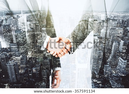 Double explosure with businessmen shaking hands and night city view - stock photo