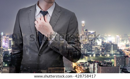 Double exposed of  businessman in gray suit with cityscape at night.
