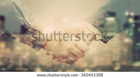 Double exposure banner of business people handshake on big city background in sunlight. Vintage colors - stock photo