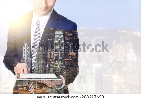 double exposure business man and city - business man using digital tablet with city night skyline, asia, china, hong kong - stock photo