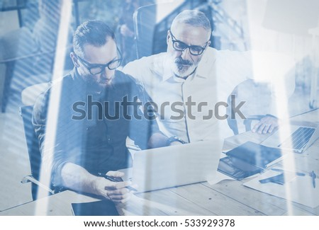 Double exposure concept.Team of business people making great work discussion in studio.Young bearded man showing statistic repot,using laptop.Skyscraper office building blurred background.Horizontal