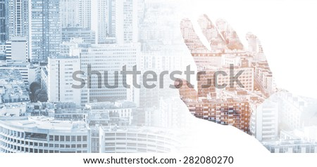 Double exposure conceptual collage with a male hand and modern big city background