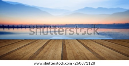 Double exposure effect of mountains and sunrise beach landscape with wooden planks floor - stock photo