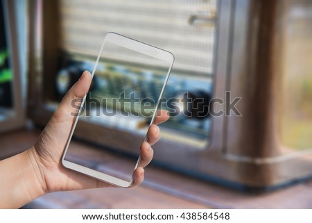 Double exposure hand holding a modern phone,using and touch smart phone,cell phone,mobile over blurred image of radio background in restaurant  - stock photo