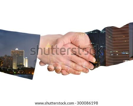 Double exposure handshake on city night background  - stock photo