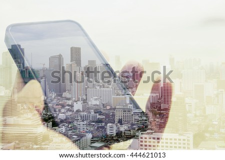 Double exposure image of using smart phone with cityscape background, Communication technology concept