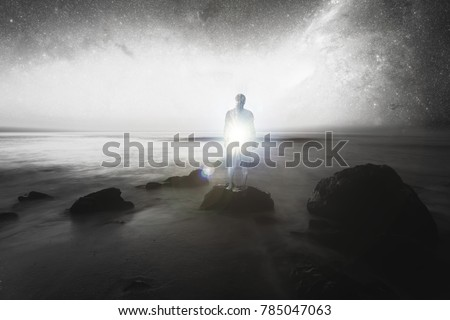 double exposure, man on the beach rocks, inside light, conceptual image, spiritual light - elements of this image are furnished by NASA