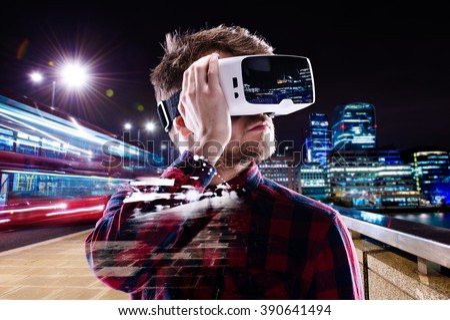 Double exposure, man wearing virtual reality goggles, night city - stock photo