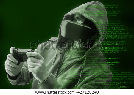 Double exposure of a caucasian man wearing a hoodie and Virtual reality ( VR ) headset is presumably a gamer or a hacker cracking the code into a secure network or server, with lines of code in green - stock photo