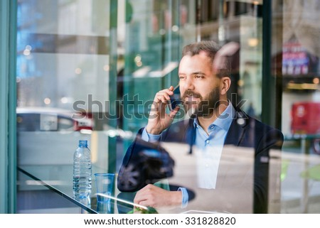 Double exposure of a handsome young man with smart phone - stock photo